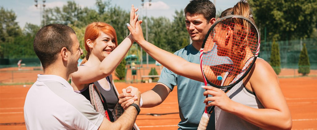 group of tennis players on tennis court giving high fives